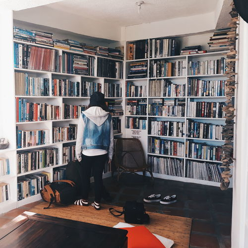 Rear view of woman standing by bookshelf