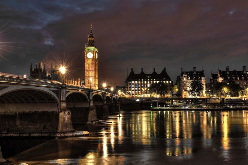 Illuminated bridge over thames river with big ben in city at night