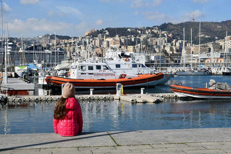 girl sitting alone Genova Italy Winter Travel Sunny Day Sunny Winter Day Travel Tranquility Relaxing Little Girl Sitting Little Girl Sea Port Cityscape Nautical Vessel Water Pier Harbor Transportation Sea Outdoors Travel Destinations Vacations Sky Day Yacht