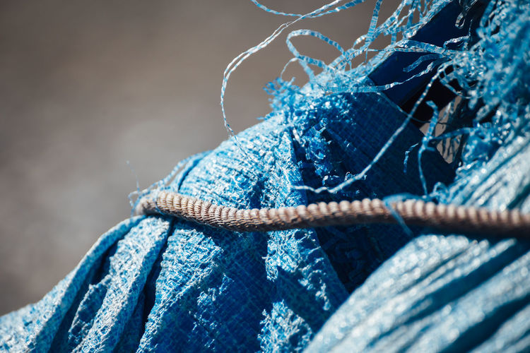 Close-up of rope on blue torn tarpaulin