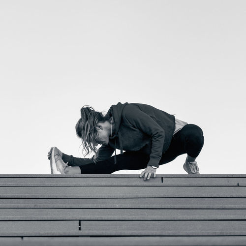 Stretching on Stairs Urban Scene Lifestyle Sport Physical Activity Motion Effort Outdoors City Riverside River Exercising Workout Action Energy Sports Clothing Athlete City Life Healthy Lifestyle One Person Sports Training Stretching Leg Square Copy Space Black And White