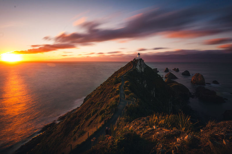 Lighthouse Beauty In Nature Cloud - Sky Horizon Horizon Over Water Idyllic Land Nature No People Non-urban Scene Orange Color Rock Rock - Object Scenics - Nature Sea Sky Sunset Tranquil Scene Tranquility Water