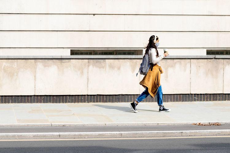 Full length of woman walking on footpath