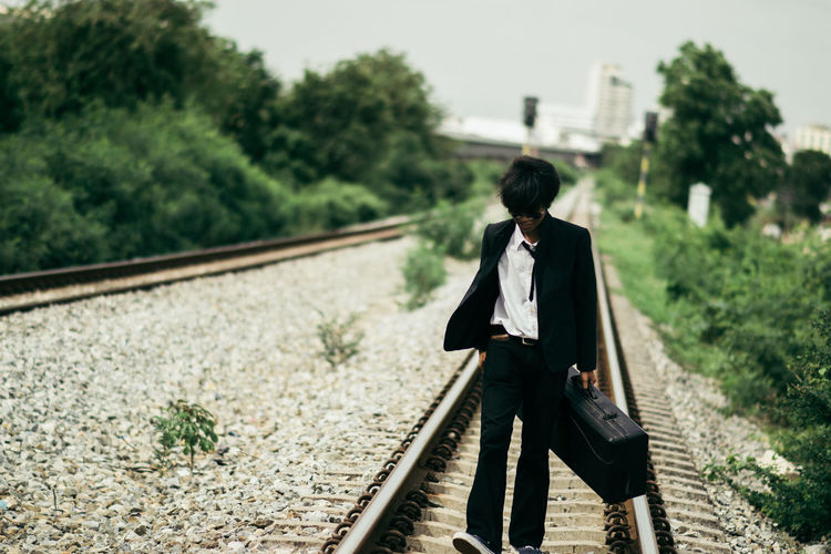 Businessman walking on railroad track
