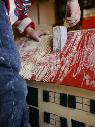 Midsection of boy coloring model house with chalk