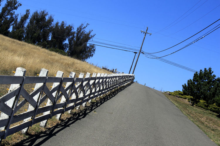 Road by electricity pylon against clear blue sky