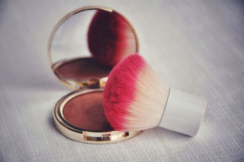 Close-up of make-up brush on blush on table