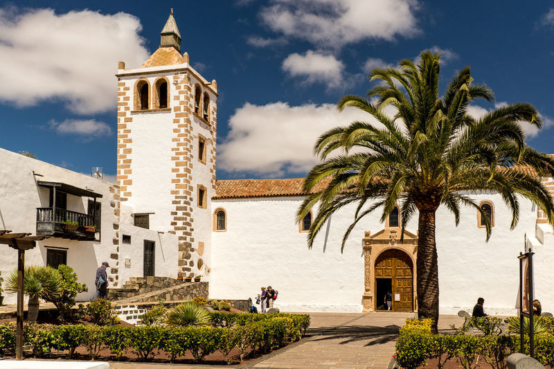 Palm trees and historical buildings against sky, fuerteventura
