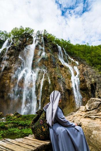 Woman sitting waterfall at plitvice lakes national park