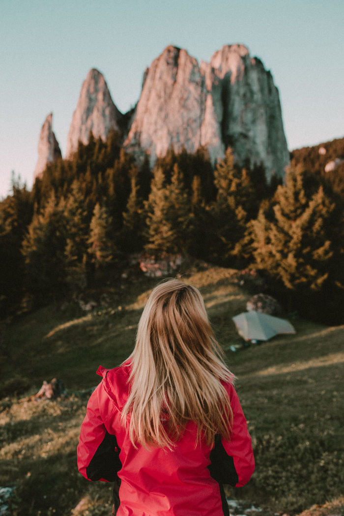 Rear view of woman looking at  mountain against clear sky