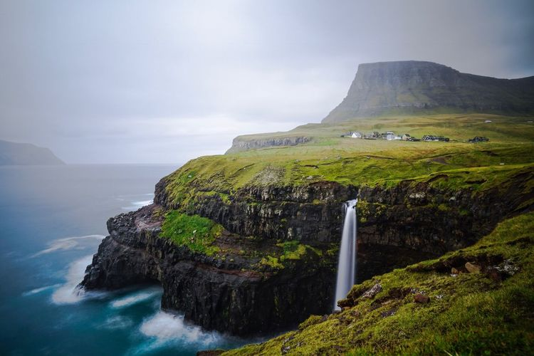 Scenic view of mountain and sea against cloudy sky at faroe islands