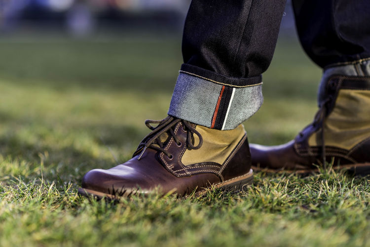 Low section of man wearing shoes on grass