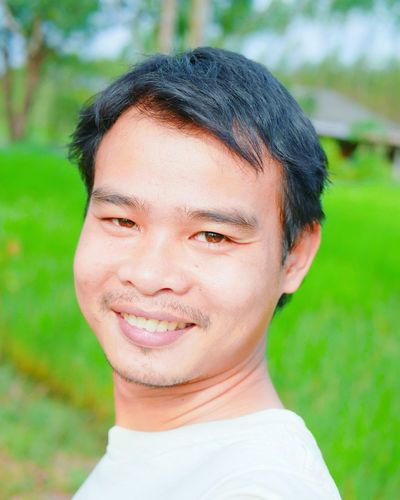 Close-up portrait of man smiling while standing at rice paddy