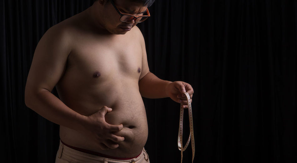 Shirtless overweight man with tape measure standing against black background