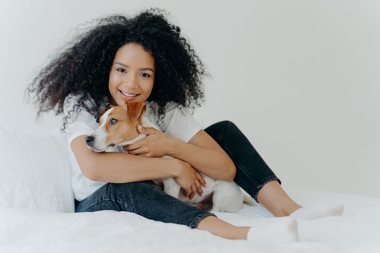 Portrait of smiling young woman with dog at home
