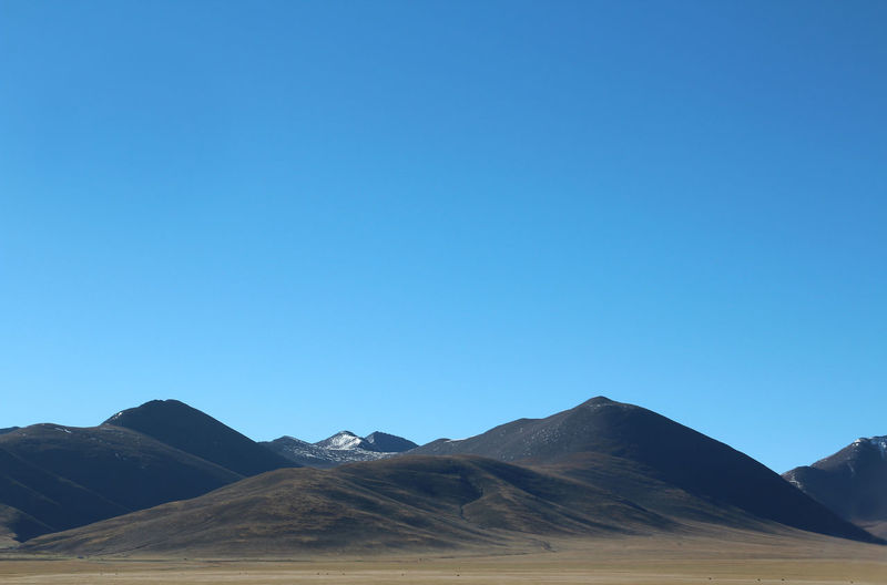 View of the Tanggula Mountains and blue sky near Namtso in Tibet, China Arid Climate Beauty In Nature Blue Blue Sky Clear Sky Copy Space Day Extreme Terrain Landscape Mountain Nature No People Outdoors Scenics Tanggula Mountains Tranquil Scene Tranquility