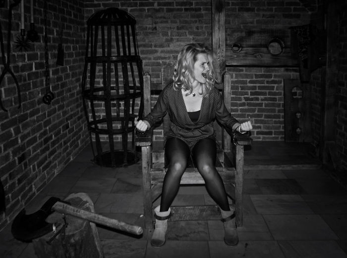 Full length of trapped woman shouting while sitting on chair