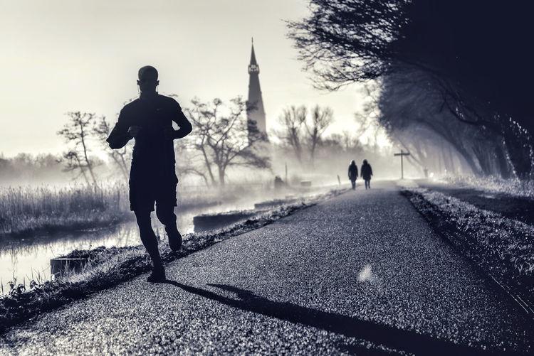 Rear view of silhouette man walking on sidewalk in city