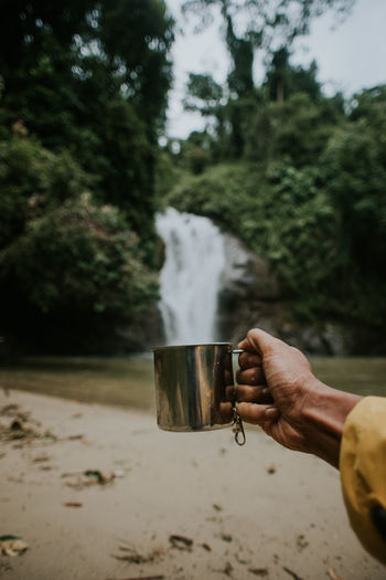 Close up shot of a man's hand holding coffee mug with waterfall in the background.camping.