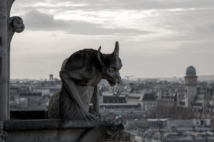 Statue of gargoyle on building in city against cloudy sky during sunset