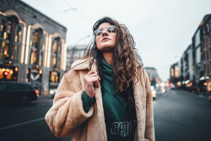 One Person City Front View Building Exterior Architecture Standing Lifestyles Young Adult Street Leisure Activity Real People Clothing Waist Up Glasses Long Hair Focus On Foreground Hairstyle Adult Young Women Hair Beautiful Woman Scarf City Street Warm Clothing Outdoors