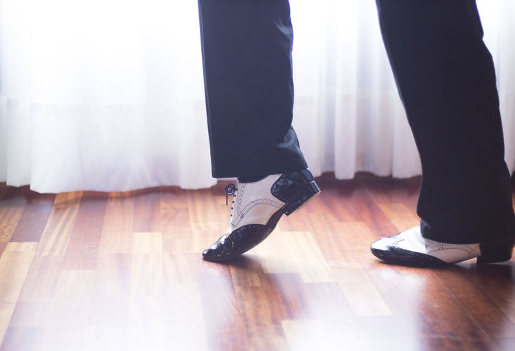 Low section of man dancing on floor at home