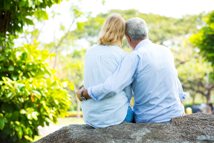 Portrait of happy Senior Couple In Park Two People Togetherness Couple - Relationship Real People Women Lifestyles Leisure Activity Adult Love Men Rear View Heterosexual Couple Day Plant Bonding Focus On Foreground Positive Emotion Nature People Casual Clothing Outdoors Arm Around Hairstyle