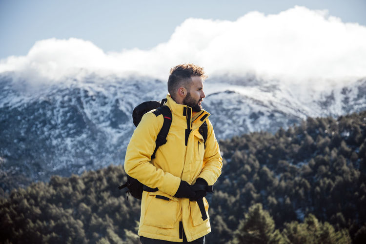 Young man standing on mountain during winter