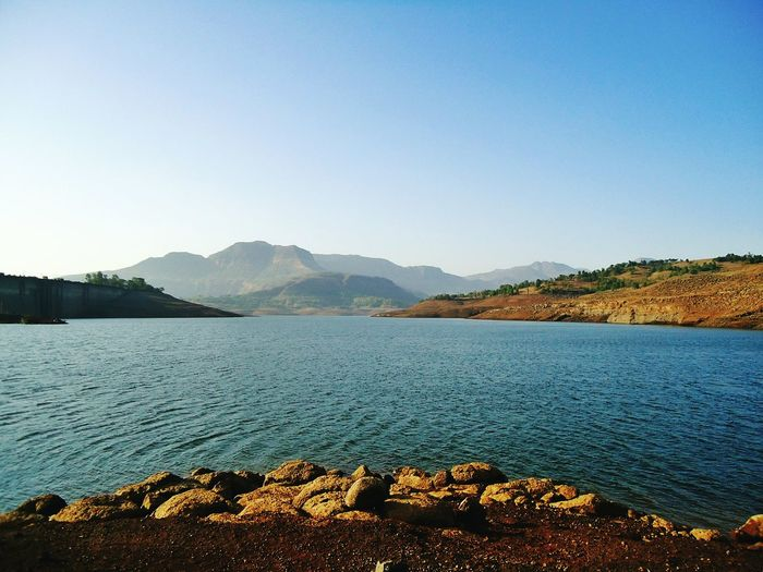 Scenic view of lake in front of mountains against clear sky