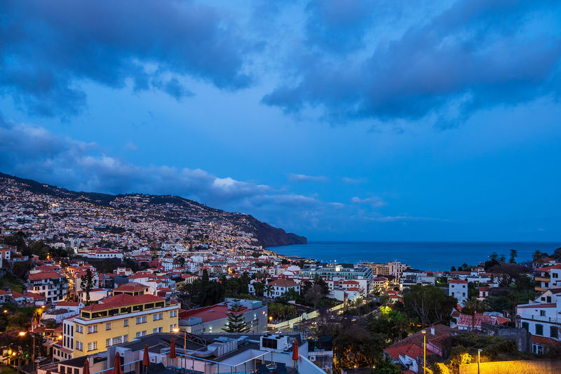 View to the city Funchal on the island Madeira, Portugal. Building Exterior Architecture Built Structure Cloud - Sky City Building Cityscape Town High Angle View Mountain Blue Outdoors Settlement Evening Night Coast Shore Atlantic Ocean Madeira Portugal TOWNSCAPE Nature