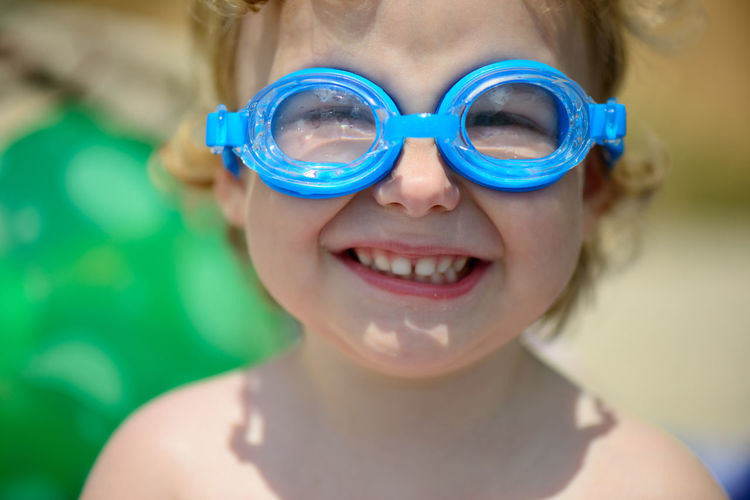 Close-up portrait of smiling girl wearing swimming goggles