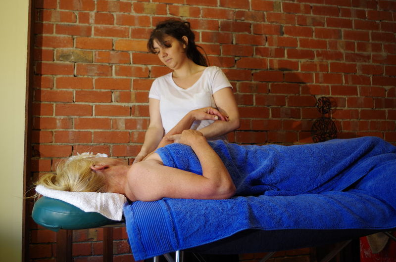 Therapist Massaging Senior Woman In Health Spa