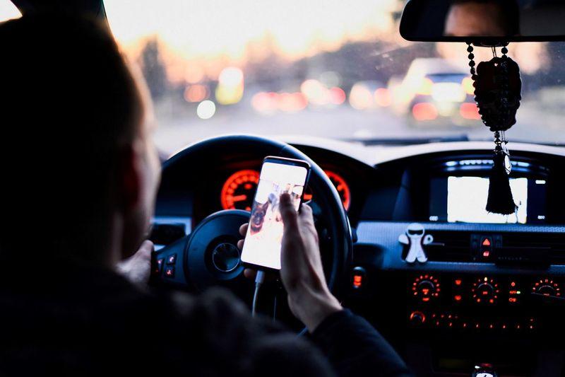 Man using phone while driving car