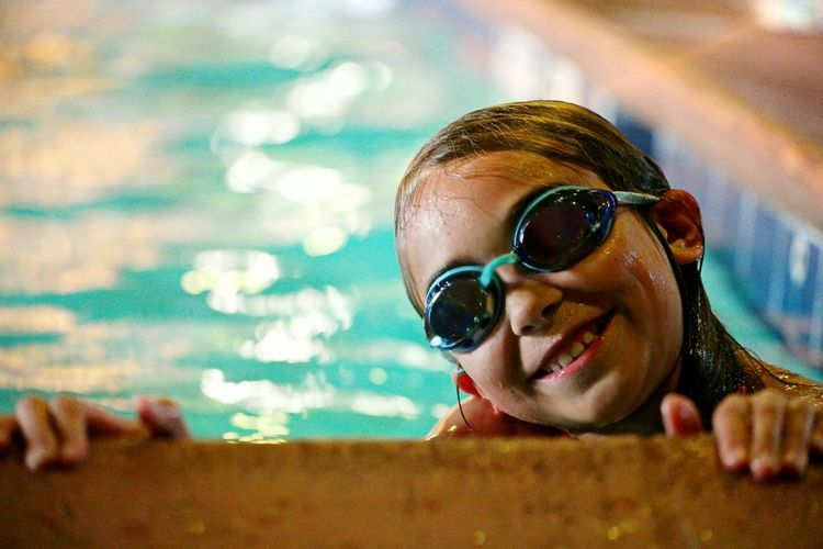 Portrait of cute girl wearing swimming goggles in pool