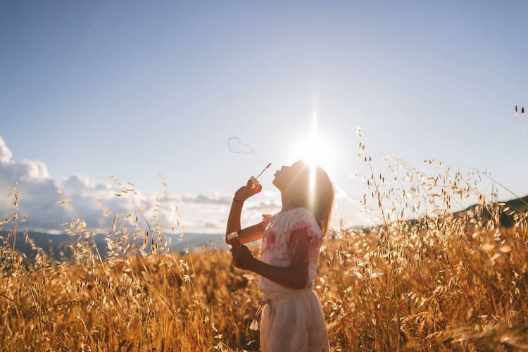 Young woman standing on field against clear sky during sunny day