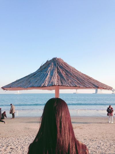 Rear view of woman standing on beach against clear sky