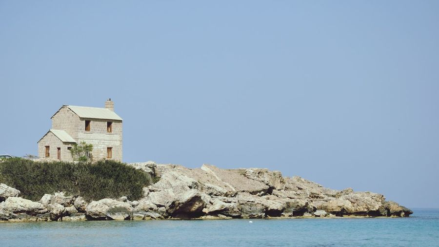 Lighthouse on cliff by sea against clear sky
