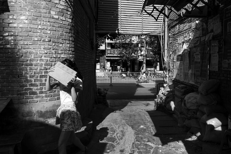 light and girl Walking Blackandwhite Lght And Shadow Built Structure Architecture Brick Building Exterior Real People Brick Wall The Street Photographer - 2018 EyeEm Awards Day Women Wall Wall - Building Feature