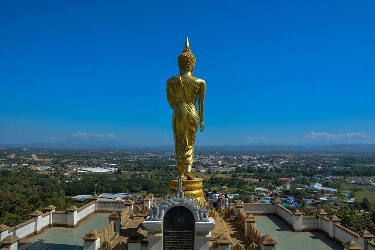 Huge buddha statue against clear blue sky