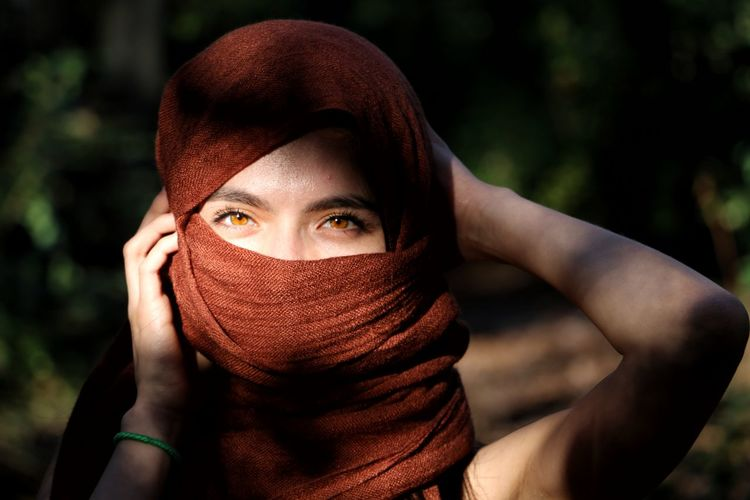 Close-up portrait of young woman hiding face outdoors