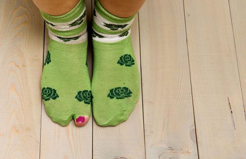 Low section of woman wearing green socks on wooden floor
