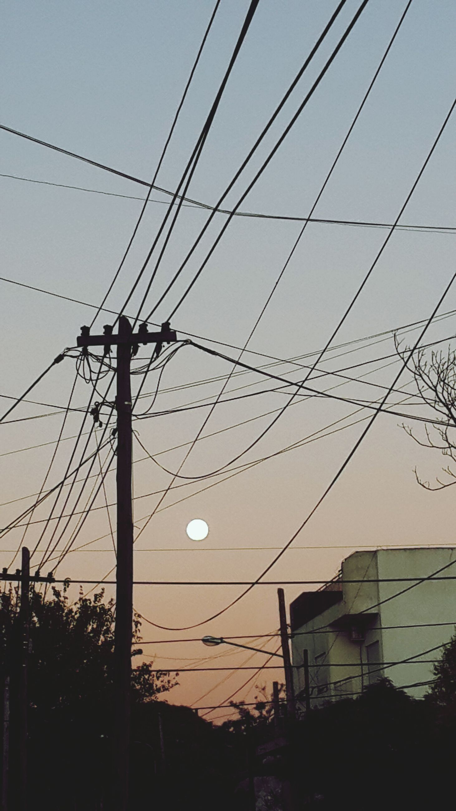 power line, electricity, electricity pylon, cable, low angle view, power supply, built structure, architecture, building exterior, silhouette, fuel and power generation, connection, sky, technology, power cable, sunset, house, street light, clear sky, dusk