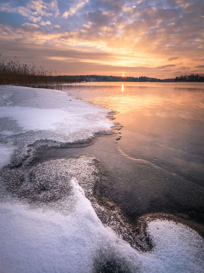 Scenic winter landscape with frozen lake and sunset at evening time in Finland Sunset Sky Beauty In Nature Cloud - Sky Scenics - Nature Water Tranquility Tranquil Scene No People Idyllic Orange Color Nature Finland Winter Lake Frost Cold Temperature Landscape Snow Reflection Moment Of Silence Season  Travel Dawn Sea