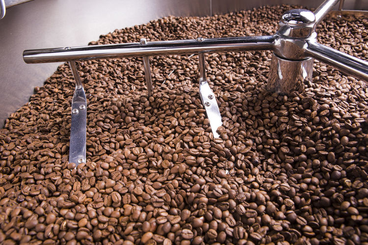 Close-up of roasted coffee beans in machinery