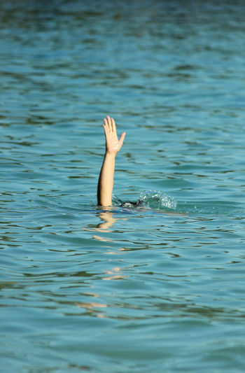Cropped Hand Of Woman Swimming In Sea