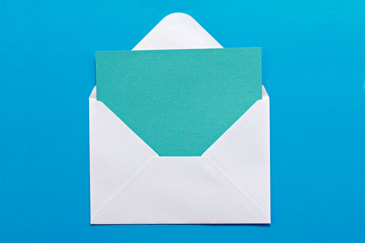 Close-up of envelope with blank paper against blue background
