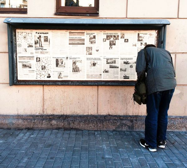 Rear view of woman against notice board on street