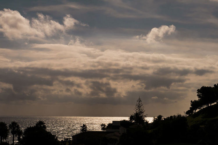 Palm trees silhouettes in a cloudy afternoon. Beauty In Nature Cloud - Sky Day Horizon Over Water Nature No People Outdoors Scenics Sea Silhouette Silhouette Silouette & Sky Sky Storm Cloud Sunset Tranquil Scene Tranquility Tree Water