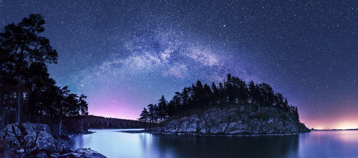 Scenic view of lake and trees against sky at night