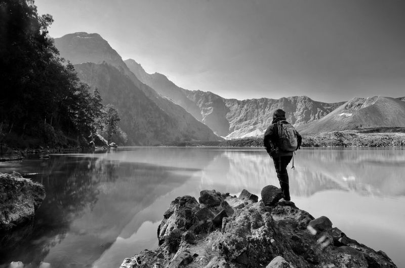 black and white Beautiful nature background with unidentified hiker at Segara Anak Lake. Mount Rinjani is an active volcano in Lombok, indonesia. Soft focus due to long exposure. Black And White EyeEm Best Shots Amazing View Nature Rinjani National Park Ilovephotography Landscape Travel Backpacking Lombok INDONESIA Base Camp Jalur Senaru Base Camp Mountain Men Snow Tree Lake Water Sky Mountain Range Hiker